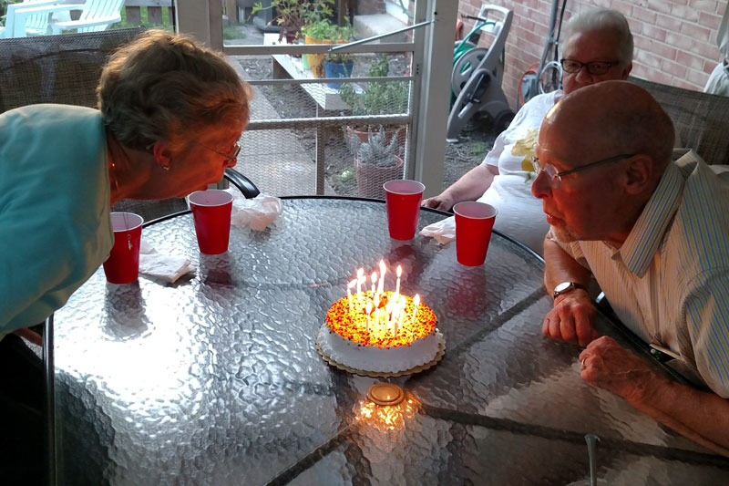 Photo of 2 people blowing out candles on a cake