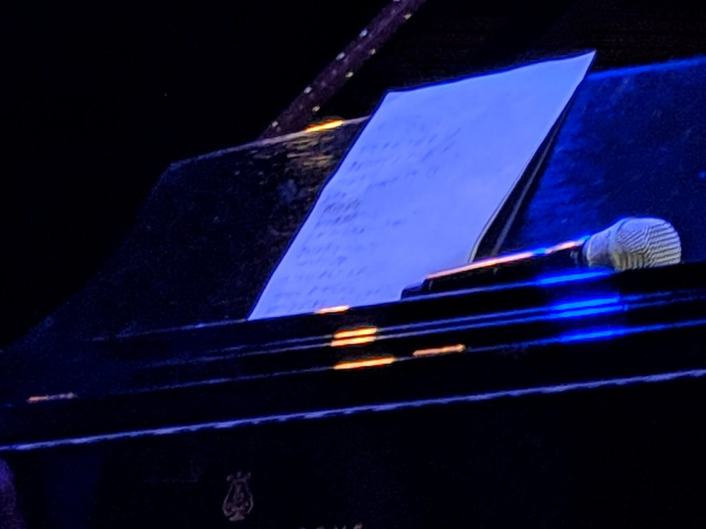 Photo of a piano with a microphone on it.