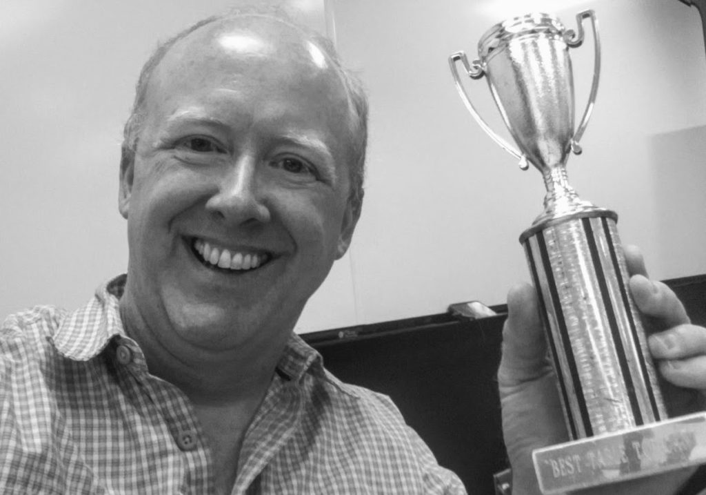 Image of guy holding a trophy.